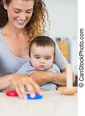 Baby looking at mother playing with toys