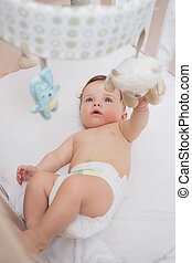 Adorable baby playing with toys in crib - High angle view of...
