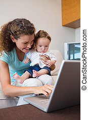 Mother showing laptop to baby - Happy mother showing laptop...