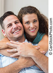Smiling woman embracing man at home