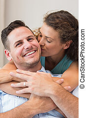 Romantic woman kissing man at home
