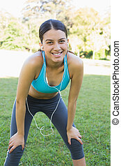 Sporty woman listening music in park - Portrait of happy...