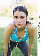 Fit woman listening music in park - Fit woman looking away...