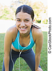 Portrait of happy fit woman listening music through...