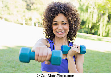 Woman lifting free weights in park - Portrait of happy young...