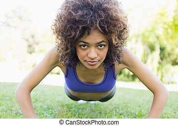 Sporty woman doing push ups in park