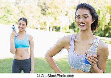 Beautiful sporty women holding water bottles - Portrait of...