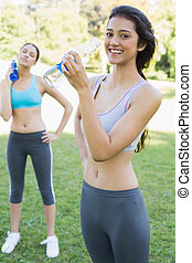 Fit women drinking water in park - Portrait of fit young...