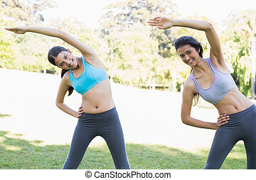 Women stretching in park