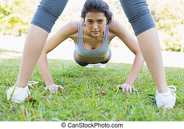 Confident woman doing push ups in park