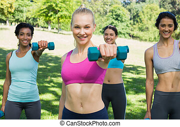 Women lifting weights in park