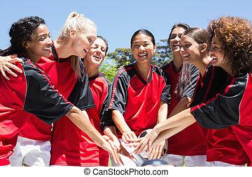 Female soccer team stacking hands - Happy female soccer team...