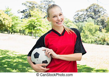 Confident female soccer player at park - Portrait of...