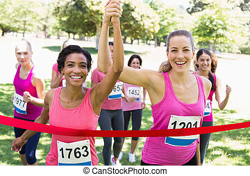Breast cancer participants crossing finish line at race -...