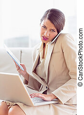 Busy and stressed businesswoman sitting on sofa multi...