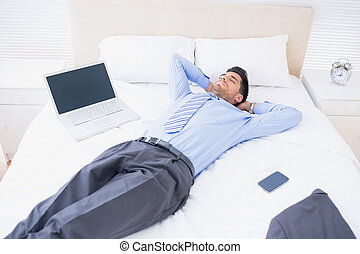 Relaxed businessman lying on his bed at home in bedroom