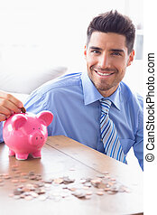 Handsome businessman putting coins into piggy bank looking...