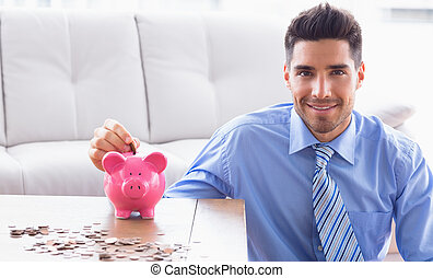 Cheerful businessman putting coins into piggy bank in the...