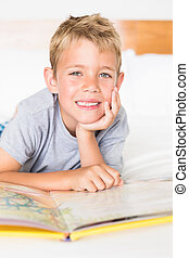 Cheerful blonde boy lying on bed reading a storybook at home...