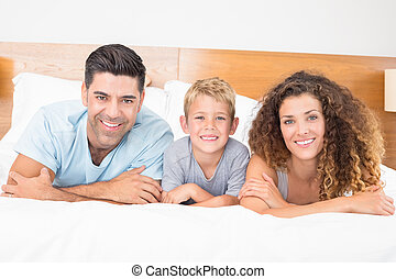 Happy young family lying on bed looking at camera at home in...