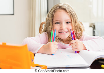 Cheerful little girl colouring at the table at home in...