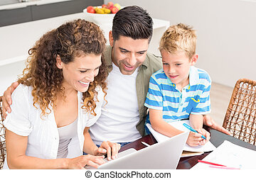 Cute little boy using laptop with his parents at table at...