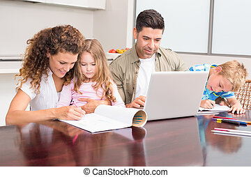 Cute young family at the table at home in kitchen