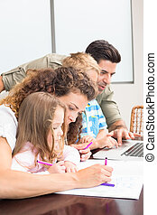 Attractive parents colouring and using laptop with their...