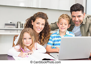 Happy parents colouring and using laptop with their children...