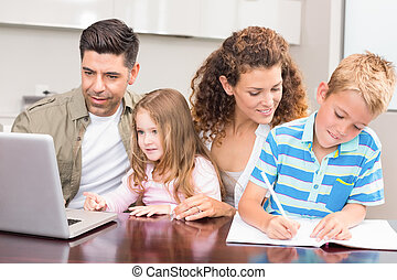 Cheerful parents colouring and using laptop with their...