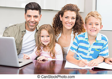 Happy parents colouring and using laptop with their young...
