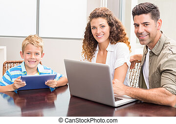 Happy parents sitting with son using tablet and laptop at...