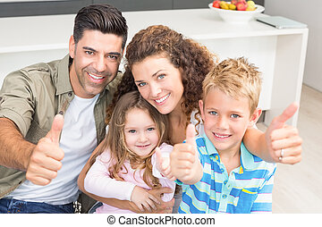 Happy parents giving thumbs up with their young children at...