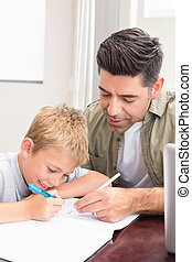 Father and son sitting at table colouring together at home...