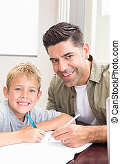 Happy father and son sitting at table colouring together at...