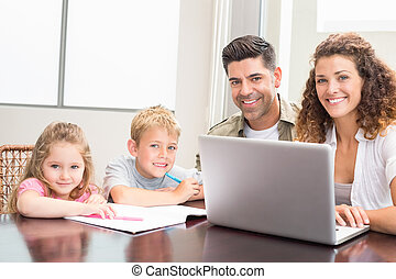 Family sitting at table with laptop and colouring book at...