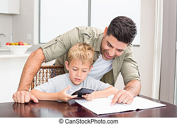 Smiling father helping son with math homework at table at...