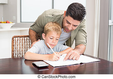 Happy father helping son with math homework at table at home...