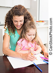 Mother and daughter colouring together at the table
