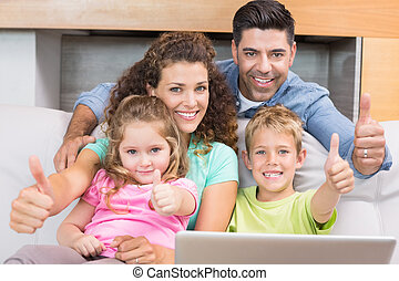 Happy family sitting on sofa using laptop giving thumbs up...