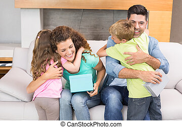 Young siblings giving presents to their parents