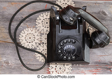 Old rotary telephone with the handset off the hook standing...