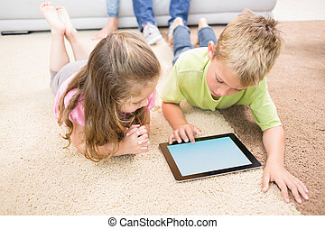 Smiling siblings lying on the rug using a tablet at home in...
