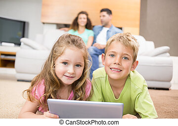 Happy siblings lying on the rug using a tablet