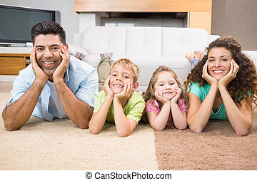 Happy siblings lying on the rug posing with their parents at...