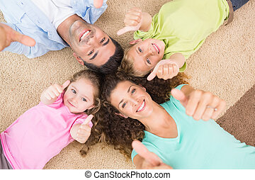 Smiling family lying on the rug in a circle showing thumbs...