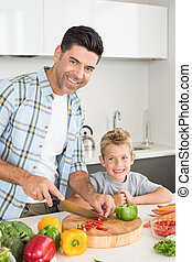 Happy father teaching his son how to chop vegetables at home...