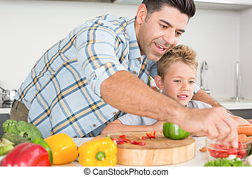 Handsome father showing his son how to prepare vegetables at...
