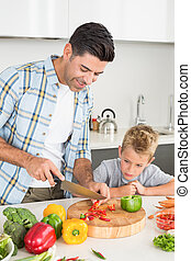 Handsome father teaching his son how to chop vegetables at...