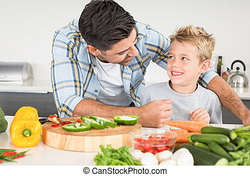 Smiling father preparing vegetables with his son at home in...
